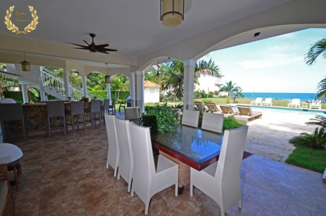 White chairs in the dining area facing the pool and ocean